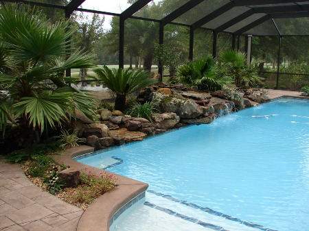 Pool Enclosure with Rock Landscape and Waterfall